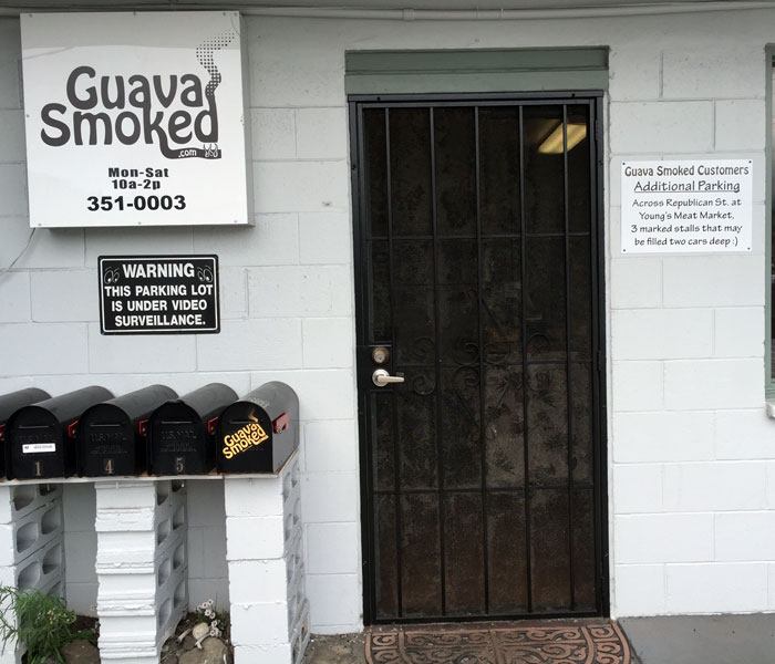 There are four parking stalls immediately in front of the Guava Smoked entrance. Additional parking is located across the street at Young's Meat Market (there are three marked stalls).