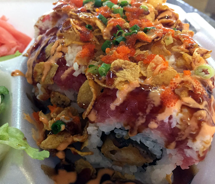 The Honey Roll includes shrimp tempura and eel, and it's topped with spicy ahi, crab, green onions, masago, the cornflake crunch and three different sauces.