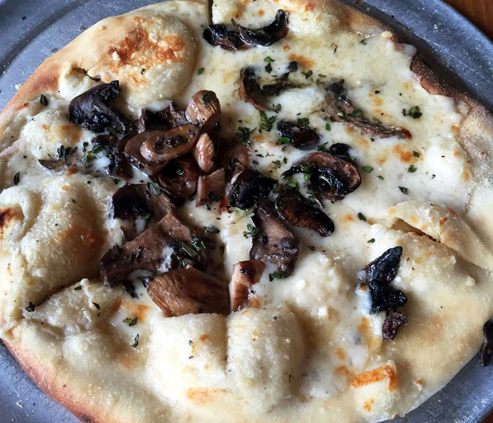 This gourmet white pizza features garlic, parmesan, fresh thyme and, of course, white sauce.