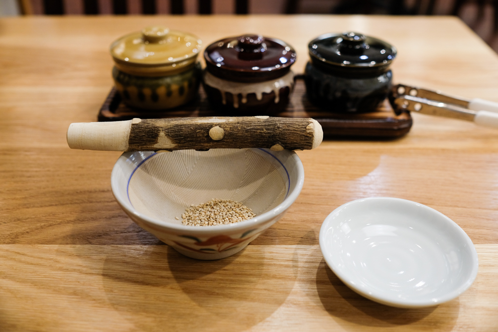 Tell-tell signs that this is the real deal: goma (sesame seeds) in a suribachi (grinding bowl) with a surikogi (grinding wood) for your katsu sauce.