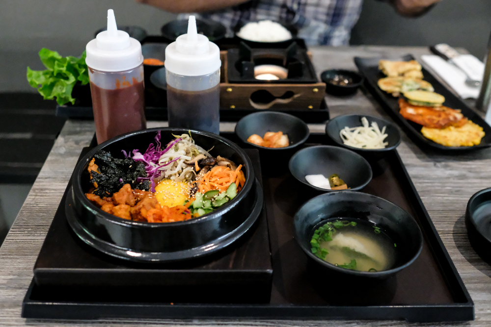 The bi bim bap arrives on a hefty tray with enormous bottles of gochujang and ganjang sauces, a few banchan and miso soup.