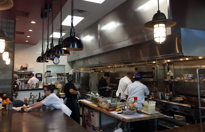 Meatery's open kitchen is bigger, with a larger counter space. Chan says there are two kitchens in Meatery — the open kitchen and the back prep kitchen. In total, the kitchen is about half the size of the restaurant.