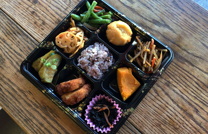 The vegetable bento consists of: eggplant, tofu patty, seaweed, kabocha, Gobo, string beans, lotus root, red bean mochi rice and a mini andagi.