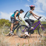 Side view of an athletic couple mountain biking