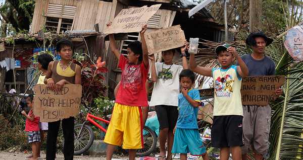 Children hold signs asking for help and food along the highway, after Typhoon Haiyan hit. Photo: Reuters