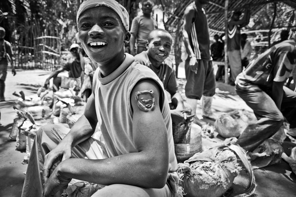 Some diggers are waiting with their minerals at the market of Ndjingala, DRC. The young man has the sign of the tiger on his arm, a symbol of Congo. Foto: Jan-Joseph Stok