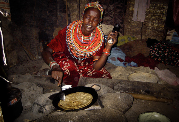 Rendille woman cooking over open fire with torch.