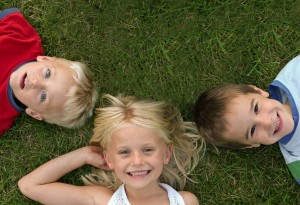 3 kids laying in grass