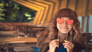 Teenage girl holding paper hearts over her eyes