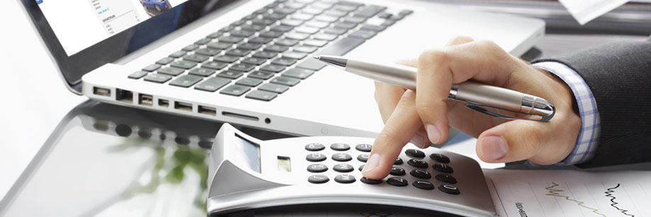 Business professional keying in on calculator with laptop open to dealership inventory page