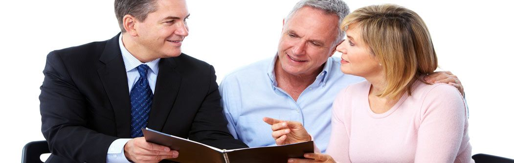 Salesman explaining paperwork to middle aged couple