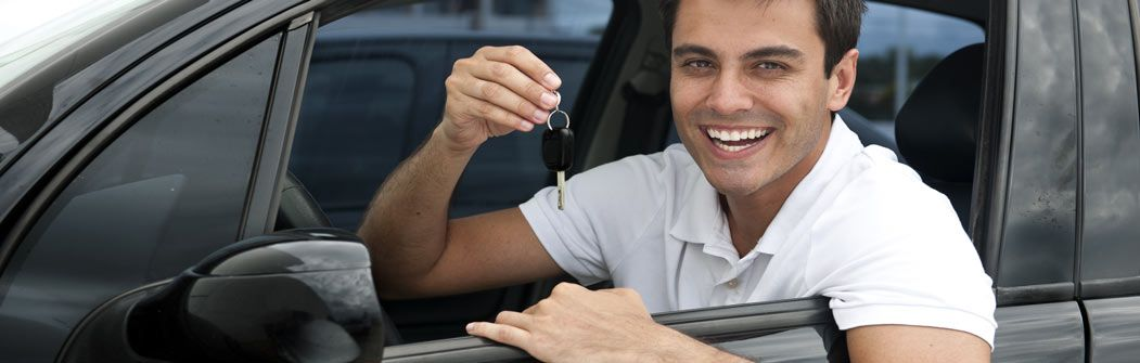 Young man in driver's seat smiling and holding up car keys