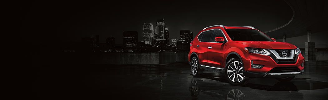 Vann York Nissan, red Rogue with dark city behind