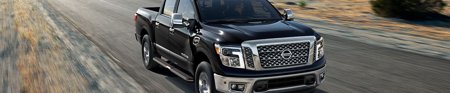 Nissan Titan, black, on dirt road