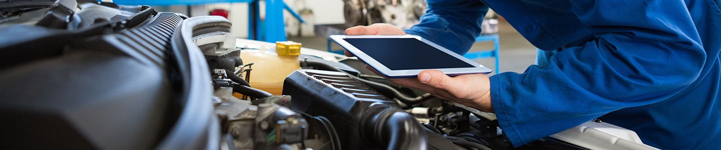 mechanic in blue leaning over engine with tablet, All Star Chevrolet North