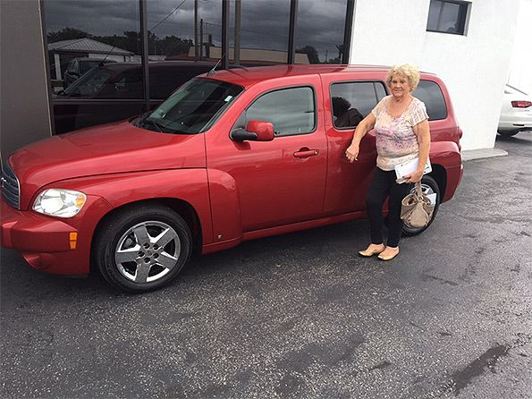 Sarasota Mitsubishi, woman standing next to new red vehicle