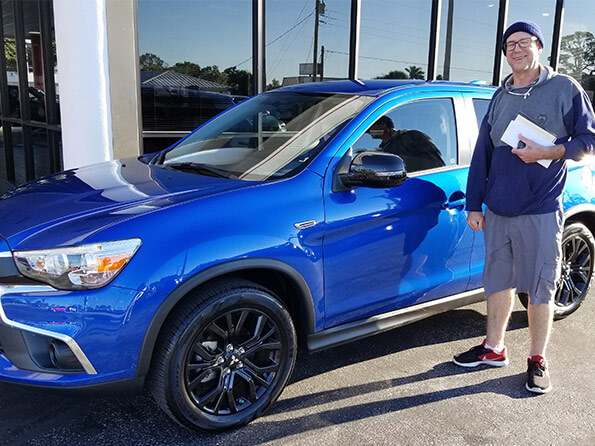 Sarasota Mitsubishi, happy guy with hat in front of new blue SUV