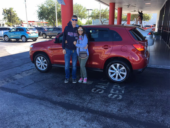 Sarasota Mitsubishi, happy couple in front of new red SUV