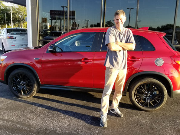 Sarasota Mitsubishi, happy guy in front of new red SUV
