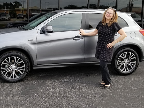 Sarasota Mitsubishi, happy woman in front of new Outlander Sport