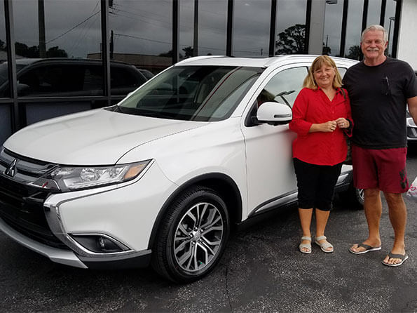Happy customers in front of new Mitsubishi Outlander