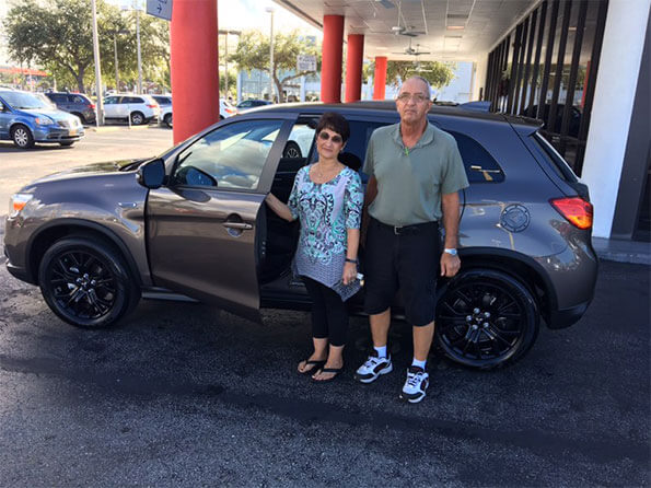 Sarasota Mitsubishi, happy customers in front of new vehicle