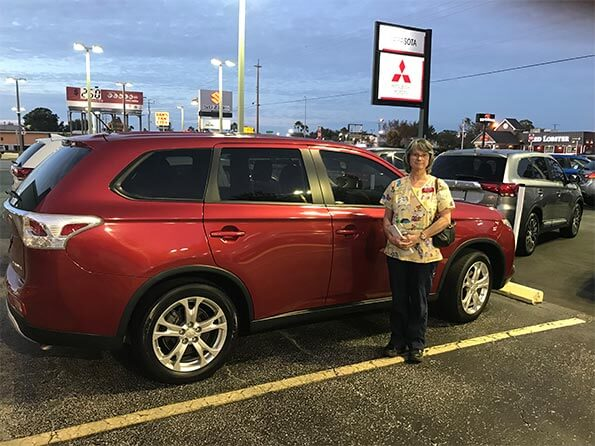 Sarasota Mitsubishi, happy woman in front of new red SUV