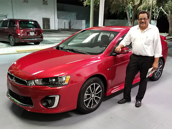 Sarasota Mitsubishi, happy guy in front of new red car