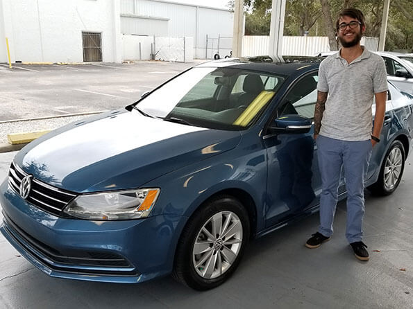 Sarasota Mitsubishi, happy guy in front of new blue Jetta