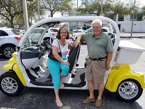 Happy couple with new yellow golf cart