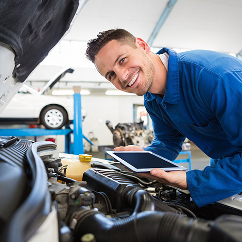 Smiling technician working on car with tablet