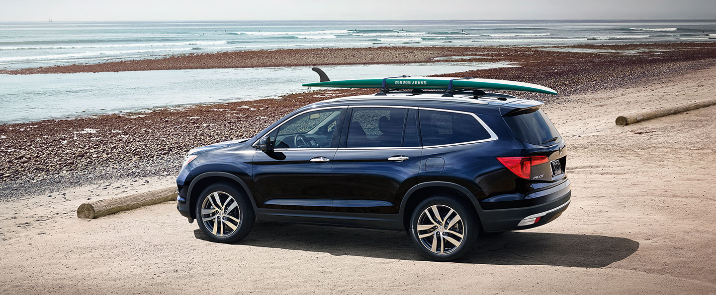 2018 Honda Pilot parked at the beach with a surfboard strapped to the roof