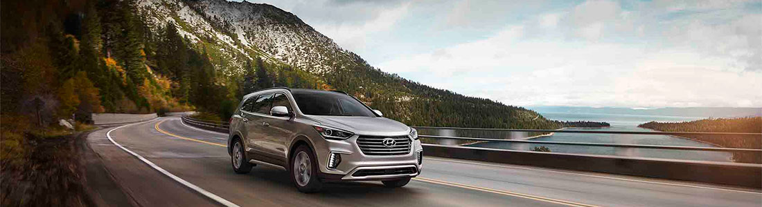 Hyundai Santa Fe driving past mountain lake