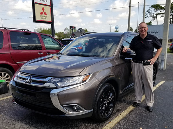 Happy guy in front of new Mitsubishi Outlander, happy customer