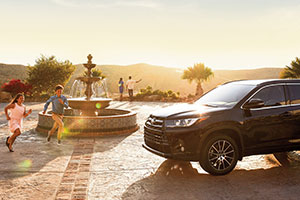 2018 Toyota Highlander parked in a sun-drenched circular driveway with children running around a fountain in the center