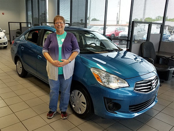 happy lady in front of new Mitsubishi Mirage
