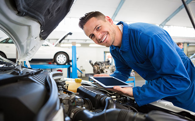 Friendly mechanic with tablet inspecting engine