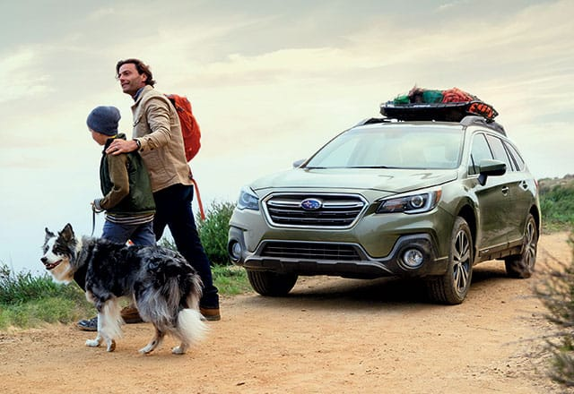 2018 Subaru Outback parked at trailhead while father, son, and dog prepare to hike