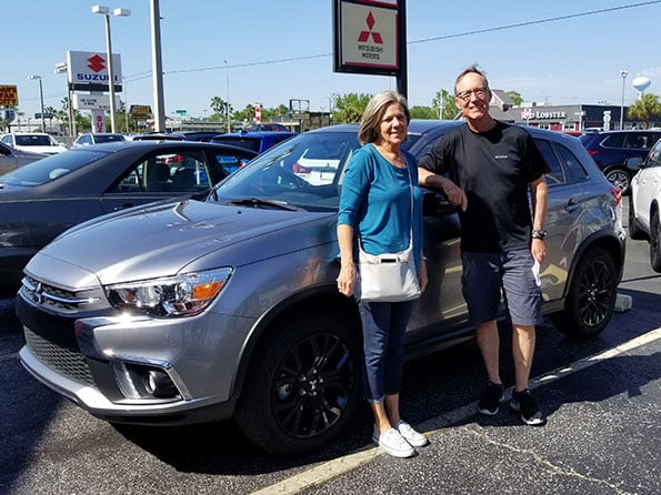 happy customers in front of mitsubishi outlander