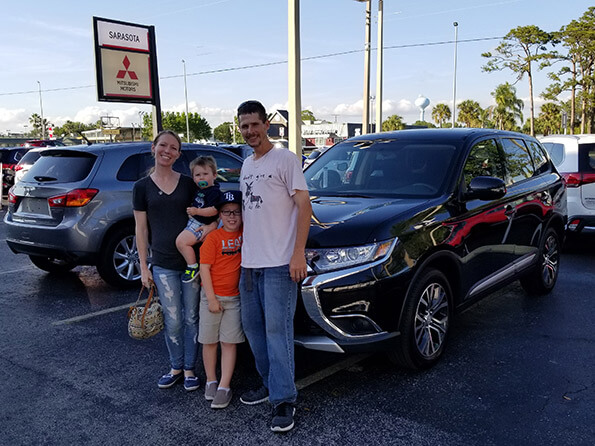 Happy Family in front of new vehicle from Sarasota Mitsubishi