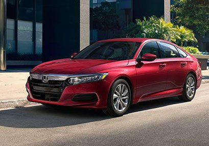 New Honda Red Accord parked on road near building