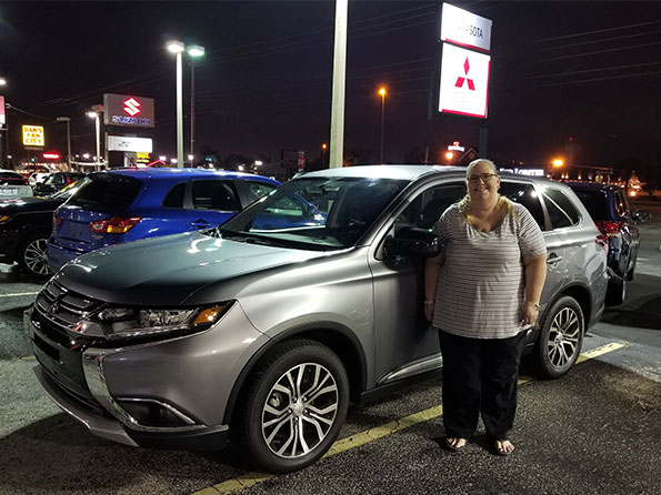 woman in front of new SUV, night time