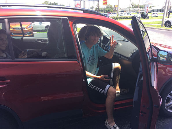 boy in vans sitting in new car