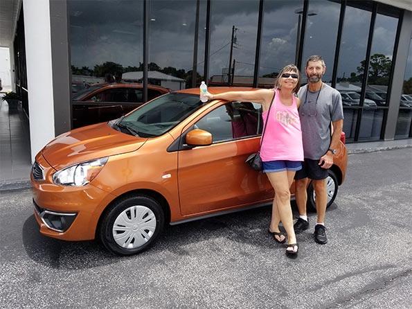 happy customers orange mistubishi car couple