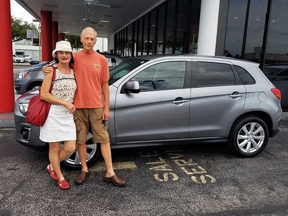 happy customer couple gray silver mitsubishi SUV Mercier Outlander