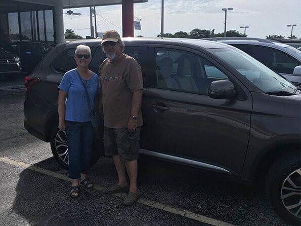 man and woman happy in front of new suv