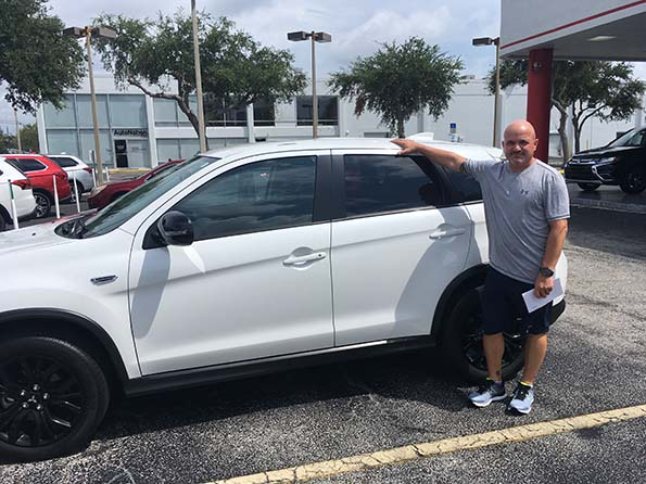man happy in front of new white car