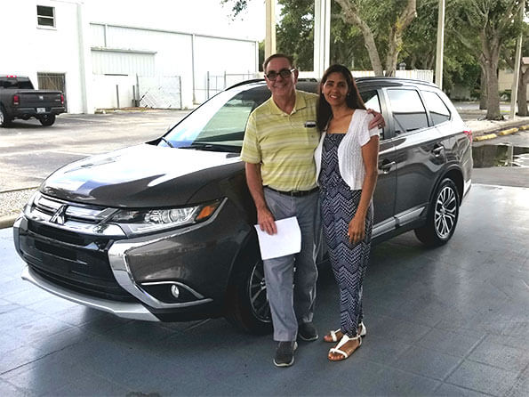 Man and woman in front of new Mitsubishi SUV