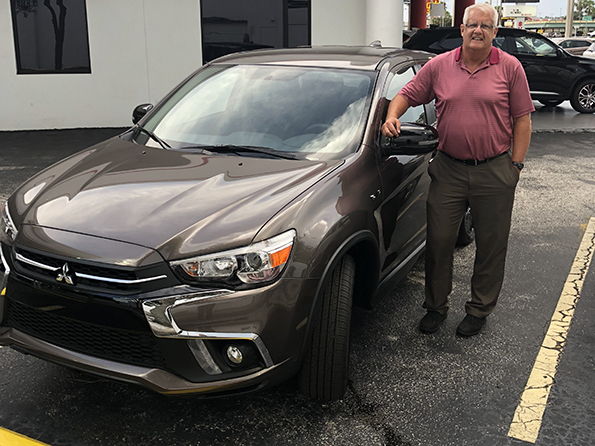 man happy in front of new brown car