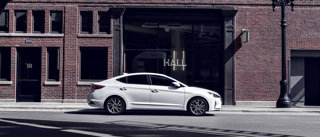 Profile view of a white 2019 Hyundai Elantra in front of a brick building